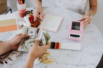 Duas pessoas sentadas ao redor de uma mesa, contando dinheiro e somando contas